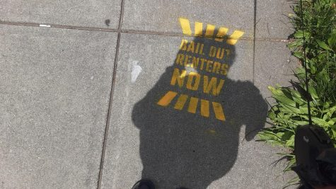 A passerby shelters the sidewalk sign from the sun. The signs of protest quietly appeared.